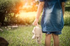 Η λαβή μικρών κοριτσιών αντέχει την κούκλα στον κήπο στοκ φωτογραφία