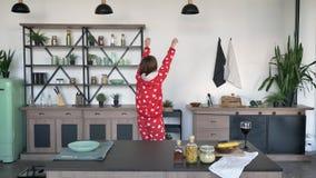 Η λατρευτή νέα γυναίκα στις αστείες πυτζάμες με ακούει να χορεψει και να στρίψει γύρω στην κουζίνα πίσω από τον πίνακα, εύθυμος κ φιλμ μικρού μήκους