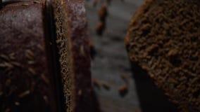 Η λεπίδα του μαχαιριού κόβει ένα κομμάτι του σκοτεινού ψωμιού απόθεμα βίντεο