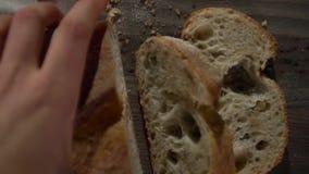 Η λεπίδα του μαχαιριού κόβει ένα κομμάτι του φλοιώδους ψωμιού απόθεμα βίντεο