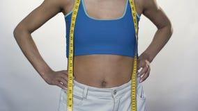 Η λεπτή γυναίκα που τραβά τη μέση του μεγάλου παντελονιού μακριά, που παρουσιάζει απώλεια βάρους, φυλλομετρεί επάνω απόθεμα βίντεο
