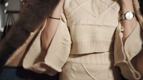 Η λεπτή γυναίκα προσπαθεί σε ένα σακάκι τζιν με τη γούνα σε ένα κατάστημα φιλμ μικρού μήκους