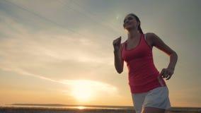 Η λεπτή γυναίκα χαμογελά και τρέχει κατά τη διάρκεια του ηλιοβασιλέματος υγιής τρόπος ζωής έννοιας φιλμ μικρού μήκους