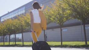 Η λεπτή επιχειρησιακή γυναίκα στο μοντέρνο κοστούμι τραβά μια βαλίτσα, πιέζει χρονικά σε μια επιχειρησιακή συνεδρίαση Ελκυστική ε φιλμ μικρού μήκους