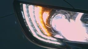 Η λεπτομέρεια του κοκκίνου επιμετάλλωσε το μαύρο οπίσθιο προβολέα αυτοκινήτων στη μορφή ματιών απόθεμα βίντεο