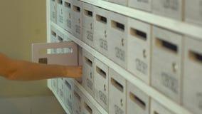 Η λευκή γυναίκα παίρνει ανοικτός την ταχυδρομική θυρίδα της στη σειρά άλλων ταχυδρομικών θυρίδων και παίρνει την επιστολή από την απόθεμα βίντεο