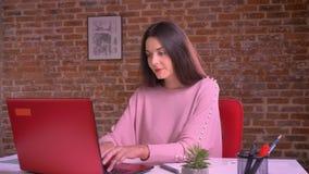 Η λευκιά ευτυχής επιχειρησιακή γυναίκα εργάζεται στο lap-top της και τη δακτυλογράφηση καθμένος στον πίνακα στο ρόδινο πουλόβερ ε απόθεμα βίντεο