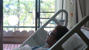 Η λυπημένη γυναίκα ηλικίας φορώντας eyeglasses βρίσκεται σε ένα νοσοκομειακό κρεβάτι με μια μάσκα οξυγόνου κάτω από μια σταλαγματ φιλμ μικρού μήκους