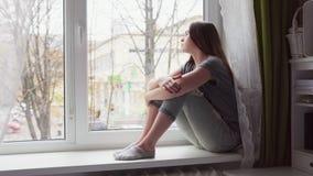Η λυπημένη γυναίκα κάθεται στο windowsill, φαίνεται έξω το παράθυρο και χαμηλώνει το κεφάλι στα γόνατα φιλμ μικρού μήκους