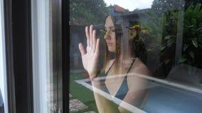 Η λυπημένη γυναίκα λέει αντίο μέσω του παραθύρου απόθεμα βίντεο