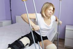 Η λυπημένη γυναίκα μετά από μια λειτουργία στο πόδι της κάθεται στο κρεβάτι στοκ φωτογραφία με δικαίωμα ελεύθερης χρήσης