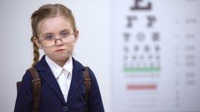 Η λυπημένη μαθήτρια στα σπασμένα γυαλιά αισθάνεται επισφαλής, φοβερισμένος από τους λόρδους για τα θεάματα φιλμ μικρού μήκους