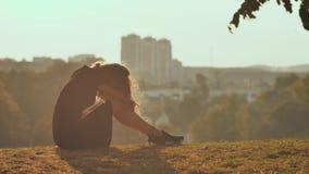 Η λυπημένη σκιαγραφία κοριτσιών κάθεται μόνο στη χλόη τόσο μόνη και την κραυγή απόθεμα βίντεο