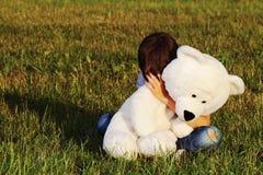 Η λυπημένη συνεδρίαση αγοριών υπαίθρια και το αγκάλιασμα teddy αντέχουν Στοκ φωτογραφία με δικαίωμα ελεύθερης χρήσης