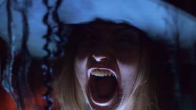 Η μάγισσα αποκριών σε ένα καπέλο κραυγάζει την κραυγή, κυνόδοντες Τρομακτικός, κινηματογράφηση σε πρώτο πλάνο, απόθεμα βίντεο