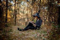Η μάγισσα αποκριών στα ξύλα διαβάζει ένα βιβλίο στα ξύλα στοκ φωτογραφίες με δικαίωμα ελεύθερης χρήσης