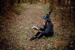 Η μάγισσα αποκριών στα ξύλα διαβάζει ένα βιβλίο στα ξύλα στοκ εικόνες με δικαίωμα ελεύθερης χρήσης