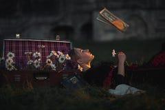 Η μάγισσα γυναικών βρίσκεται και διαβάζει ένα βιβλίο μετεωρισμός Στοκ Φωτογραφία