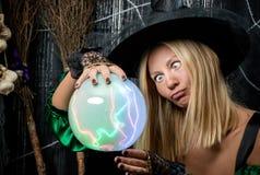 η μάγισσα εξετάζει μια μαγική σφαίρα Στοκ Φωτογραφία