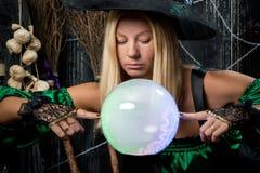 Η μάγισσα εξετάζει τη μαγική σφαίρα του και προσπαθεί να δει Στοκ Φωτογραφία