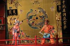 Η μάχη, όπερα του Πεκίνου, στο στάδιο ένας αρσενικός πολεμιστής και θηλυκός πολεμιστής στα φωτεινά παραδοσιακά ενδύματα Στοκ Φωτογραφία