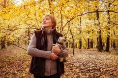 Η μέσης ηλικίας γυναίκα πίνει το τσάι στο δάσος φθινοπώρου Στοκ φωτογραφία με δικαίωμα ελεύθερης χρήσης