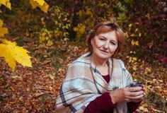 Η μέσης ηλικίας γυναίκα πίνει το τσάι στο δάσος φθινοπώρου Στοκ φωτογραφίες με δικαίωμα ελεύθερης χρήσης