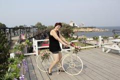 Η μέσης ηλικίας γυναίκα στα ενδύματα για τις υπαίθριες δραστηριότητες κάθεται στο ποδήλατο Στοκ Φωτογραφία