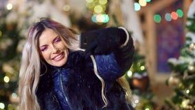 Η μέση βλασταημένη λήψη γυναικών χαμόγελου selfie που χρησιμοποιεί το smartphone στο χριστουγεννιάτικο δέντρο ανάβει bokeh το υπό απόθεμα βίντεο