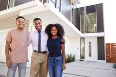 Η μέση ηλικίας άγαμη μητέρα αφροαμερικάνων και τα παιδιά της που στέκονται μπροστά από το σύγχρονο σπίτι τους, κλείνουν επάνω στοκ φωτογραφίες