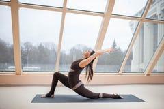 Η μέση ηλικίας έννοια γιόγκας άσκησης γυναικών γιόγκη ελκυστική, που στέκεται στην άσκηση αναβατών αλόγων, anjaneyasana θέτει μπρ Στοκ Εικόνες