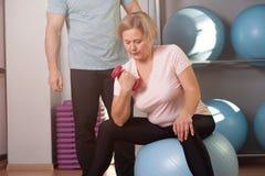 Η μέση ηλικίας γυναίκα είναι δεσμευμένη στο fitball στοκ φωτογραφία με δικαίωμα ελεύθερης χρήσης