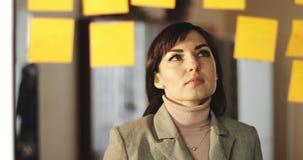 Η μέση ηλικίας επιχειρησιακή γυναίκα κολλά τις μικρές αυτοκόλλητες ετικέττες στο γυαλί στο γραφείο φιλμ μικρού μήκους