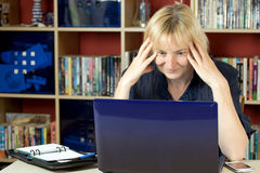 Η μέση ηλικίας γυναίκα διαβάζει στο σημειωματάριο στοκ φωτογραφία με δικαίωμα ελεύθερης χρήσης