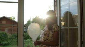 Η μέση ηλικίας γυναίκα στέκεται στις ανοικτές πόρτες μπαλκονιών με το μπαλόνι στα χέρια της φιλμ μικρού μήκους