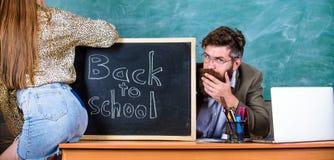 Η μίνι φούστα σπουδαστών με τους προκλητικούς γλουτούς παραπλανεί το δάσκαλο Σπάζοντας κανόνες Κανόνες πειθαρχίας σχολικής συμπερ στοκ εικόνα