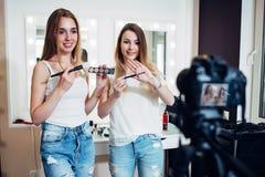 Η μαγνητοσκόπηση δύο bloggers ομορφιάς σκιές ματιών και βούρτσες μιας makeup αγορών οδηγών επίδειξης ενάντια αποτελεί τους καθρέφ στοκ φωτογραφία