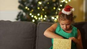 Η μαθήτρια ανοίγει μια συνεδρίαση δώρων στον καναπέ κοντά στο χριστουγεννιάτικο δέντρο Το κορίτσι είναι και απογοητευμένο με το δ απόθεμα βίντεο