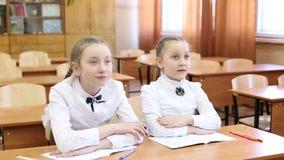 Η μαθήτρια αυξάνει το χέρι της για να απαντήσει στην ερώτηση δασκάλων απόθεμα βίντεο