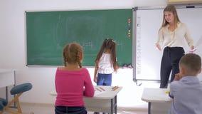 Η μαθήτρια γράφει ένα απλό παράδειγμα στον πίνακα κιμωλίας κοντά στον εκπαιδευτικό στο μάθημα math, βασική εκπαίδευση φιλμ μικρού μήκους