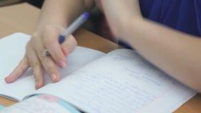 Η μαθήτρια γράφει στο σημειωματάριο με τη μάνδρα ballpoint απόθεμα βίντεο
