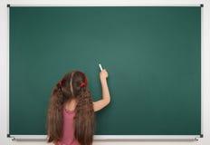 Η μαθήτρια γράφει στο σχολικό πίνακα Στοκ Εικόνες