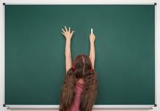 Η μαθήτρια γράφει στο σχολικό πίνακα Στοκ φωτογραφίες με δικαίωμα ελεύθερης χρήσης