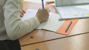 Η μαθήτρια γράφει το κείμενο σε ένα copybook χρησιμοποιώντας τη μάνδρα φιλμ μικρού μήκους