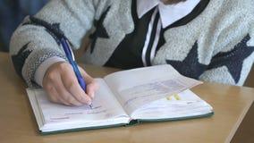 Η μαθήτρια γράφει το κείμενο στο σημειωματάριο στο εσωτερικό απόθεμα βίντεο