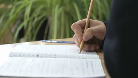 Η μαθήτρια γράφει το κείμενο στο σημειωματάριο χρησιμοποιώντας το μολύβι απόθεμα βίντεο