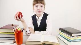 Η μαθήτρια κάθεται με το βιβλίο και τρώει το κόκκινο μήλο απόθεμα βίντεο