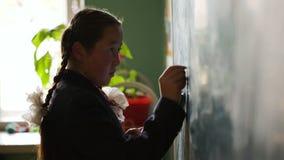 Η μαθήτρια σε ομοιόμορφο γράφει με την κιμωλία εν πλω απόθεμα βίντεο