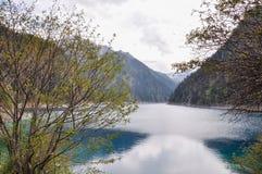 Η μακριά λίμνη είναι σκούρο μπλε και από τη σειρά των πράσινων λόφων. Στοκ φωτογραφίες με δικαίωμα ελεύθερης χρήσης