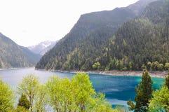 Η μακριά λίμνη είναι σκούρο μπλε και από τη σειρά των πράσινων λόφων. Στοκ φωτογραφία με δικαίωμα ελεύθερης χρήσης